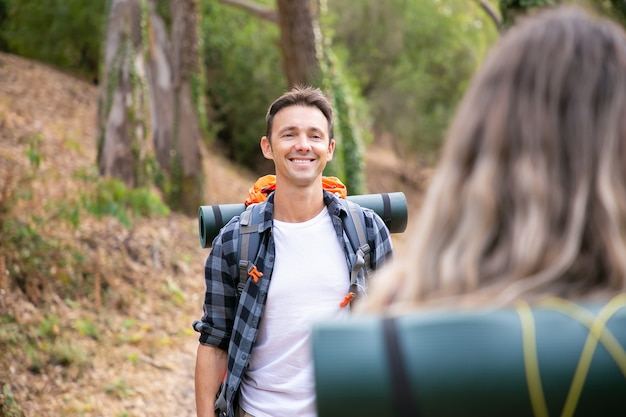 Happy caucasian man standing in woods and smiling. cheerful hiker walking in forest with blonde woman, enjoying nature, carrying backpack and posing. tourism, adventure and summer vacation concept