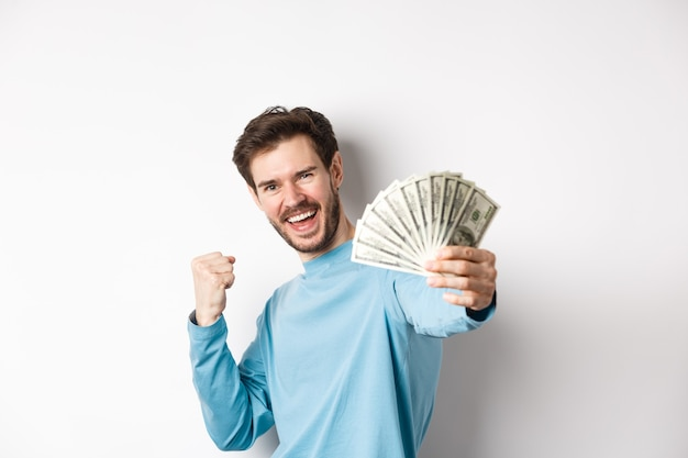Happy caucasian man stretch out hand with money in dollars, saying yes and celebrating income, got cash prize, standing over white background.