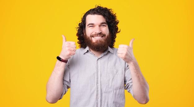 Счастливый кавказский мужчина с длинными волосами и бородой показывает палец вверх и улыбается в камеру