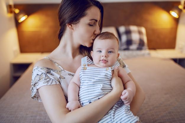 寝室のベッドの上に座って、彼女の生後6ヶ月の息子を抱いてキスした幸せな白人の母。赤ちゃんが喜んでいる表情。