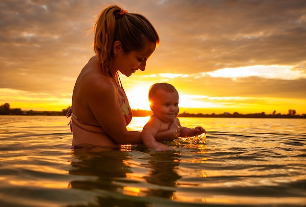 Happy caucasian mother swimming with little cute smiling baby in sea