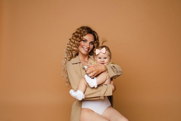 Счастливая кавказская мать с красивыми волнистыми волосами, улыбаясь в камеру, обнимая свою прекрасную дочь с бантом на голове. изолированный.