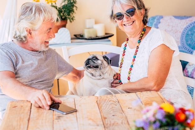 Счастливая кавказская старая старшая пара развлекается вместе со своей милой старой мопсой, сидящей на стуле