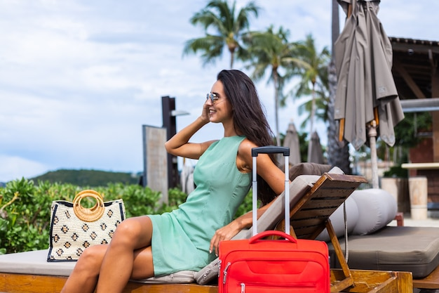 Happy caucasian pretty long hair elegant tourist woman in dress with red suitcase outside hotel
