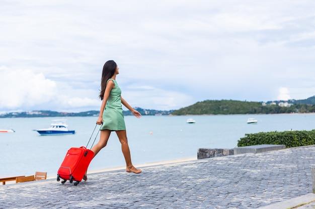 Счастливая кавказская довольно длинными волосами, элегантная туристическая женщина в платье с красным чемоданом возле отеля