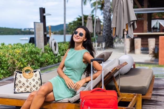 ホテルの外で赤いスーツケースとドレスを着た幸せな白人のかなり長い髪のエレガントな観光客の女性