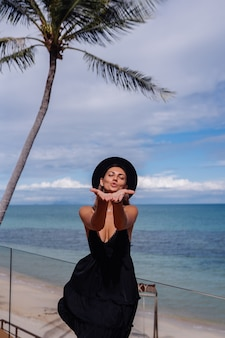 Счастливая кавказская красивая женщина в отпуске, улыбаясь в черном платье и классической шляпе, пальме и море