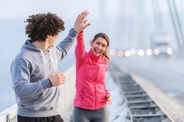Счастливые кавказские бегуны дают высокие пять во время бега по мосту в холодную погоду. снег вокруг, зима.