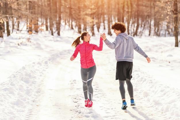 寒い気候での実行中にハイファイブを与える幸せな白人ランナー。冬は雪が降ります。
