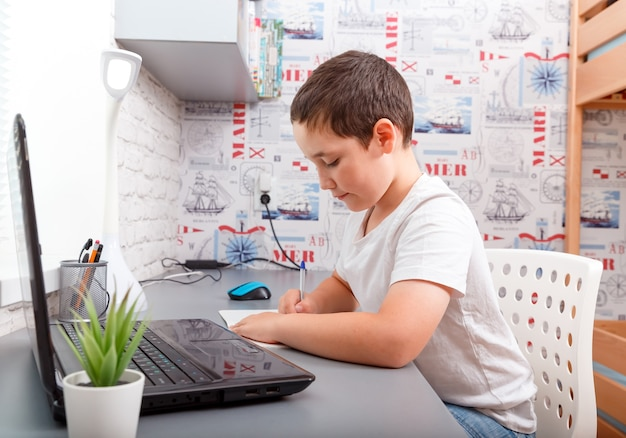 Happy caucasian schoolboy doing homework sitting at desk homeschooling