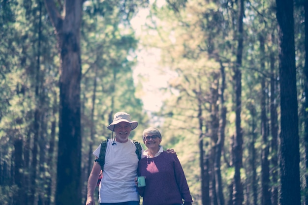 Happy caucasian senior couple smile and enjoy the travel with backpack in the outdoor nature forest - alternative free vacation concept for aged people - joyful lifestyle and hug and love