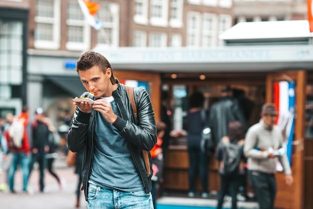 암스테르담 전통 d.에서 양파와 네덜란드 국기와 함께 신선한 청어와 행복한 백인 관광객 ...