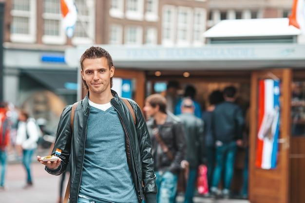 암스테르담에서 양파와 네덜란드 국기와 함께 신선한 청어와 함께 행복 한 백인 관광객. 전통적인 네덜란드 음식 야외