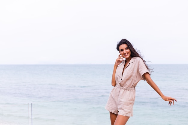 Happy caucasian woman in beige stylish trebdy jumpsuit at windy cloudy day in the beach