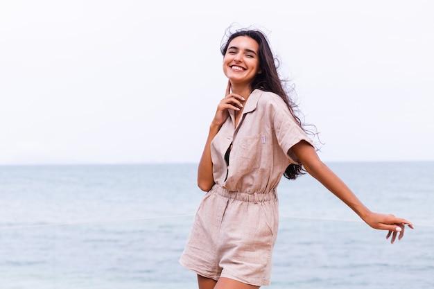 Donna caucasica felice in tuta trebdy elegante beige al giorno nuvoloso ventoso in spiaggia