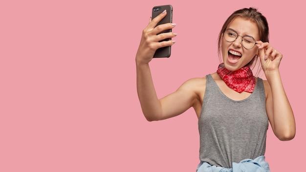 幸せな白人女性が目を瞬き、現代のスマートフォンで自分撮りのポーズをとる