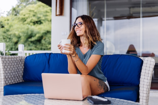 Happy caucasian woman does distance work on laptop at home comfortable place drinking tea
