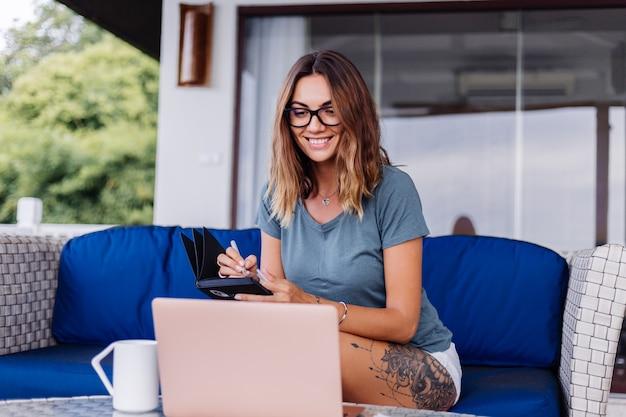 幸せな白人女性はお茶を飲む自宅の快適な場所でラップトップで遠隔作業を行います
