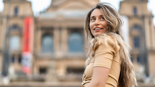 Happy caucasian woman in dress with view of barcelona on the background, spain