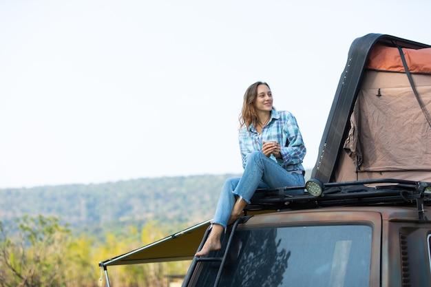 Счастливая кавказская женщина наслаждается красивым отдыхом в машине с палаткой на крыше. автомобиль караван на красивый отпуск