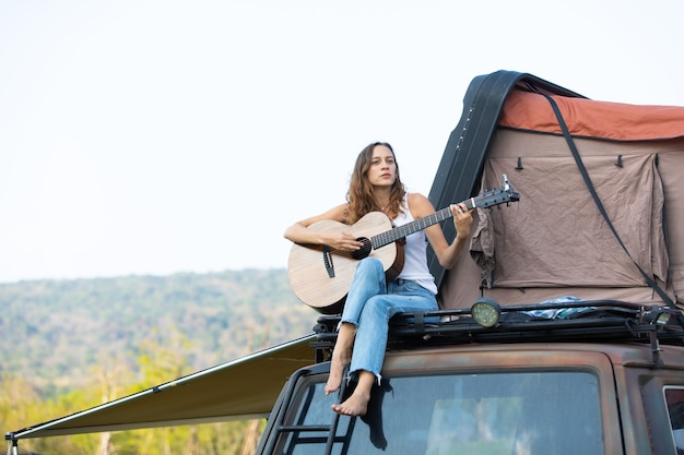 Счастливая кавказская женщина наслаждается игрой на гитаре и поет песню красивых каникул в машине с палаткой на крыше. автомобиль караван на красивый отпуск