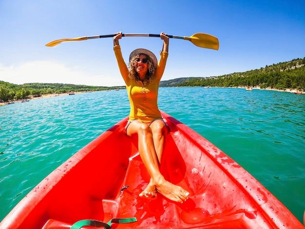 晴れた日の間に湖の赤いカヌーに座ってオールを保持している幸せな白人女性。夏のカヌーに乗って楽しんで両腕を上げてオールを持って美しい女性観光客