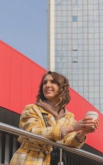 Счастливая кавказская женщина в желтом пальто с чашкой кофе, чтобы пойти на прогулку по городу