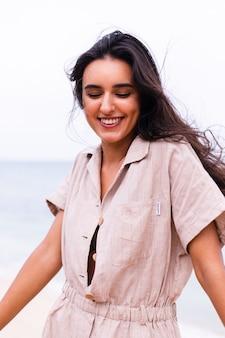ビーチで風の強い曇りの日にベージュのスタイリッシュなtrebdyジャンプスーツで幸せな白人女性