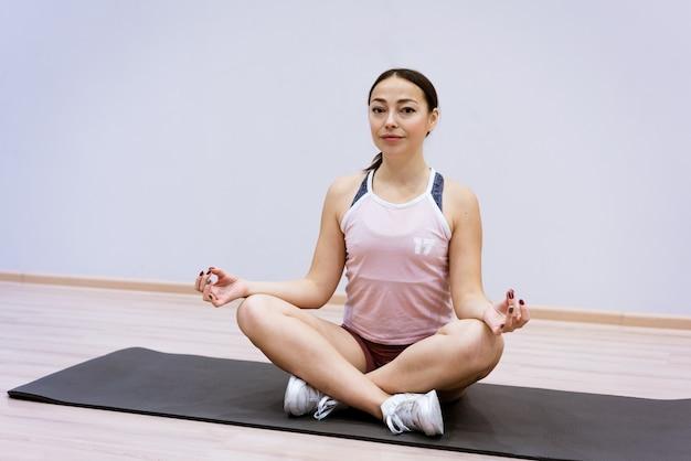 운동복을 입은 행복한 백인 여성은 집에서 벽을 배경으로 요가를 연습합니다. 건강한 생활 방식과 내면의 정신의 개념. 신체 집중