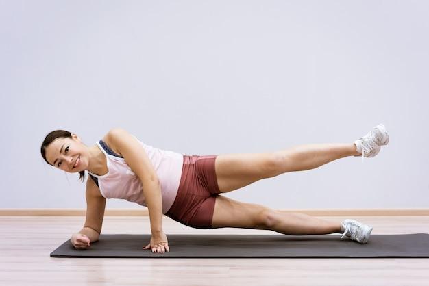 운동복에 행복 백인 여자는 벽에 집에서 요가를 실천 건강한 라이프 스타일과 내면의 정신 몸 농도의 개념