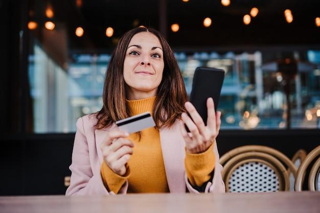 Счастливая кавказская женщина на террасе, используя устройство мобильного телефона и кредитную карту для покупок в интернете. концепция технологии и образа жизни