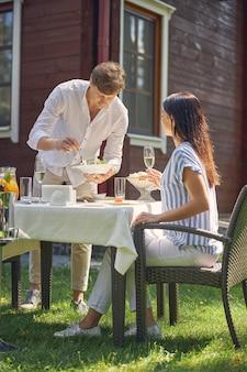 彼女の男と休んでいる間シャンパングラスを手に持っている白と青のブラウスで幸せな白人女性