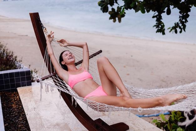 幸せな白人女性はビーチでピンクのビキニのハンモックに横たわっています