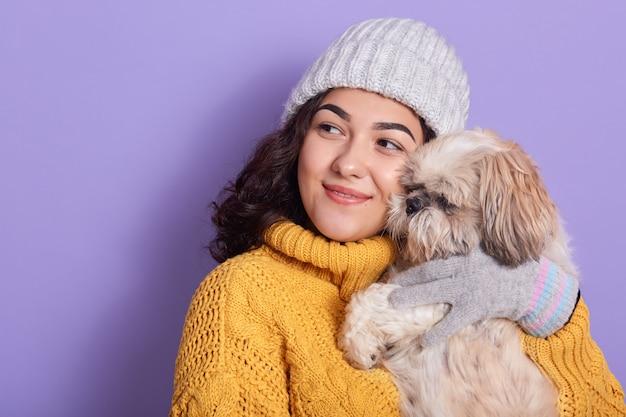 幸せな白人女性が目をそらし、小さな子犬を運ぶ、他の犬と友達に気づいて喜んで