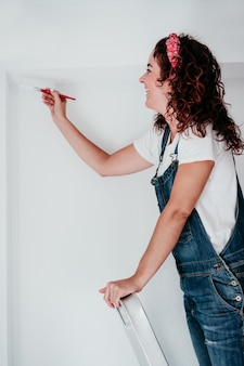 Happy caucasian woman painting the room walls with white color. do it yourself and new home concept