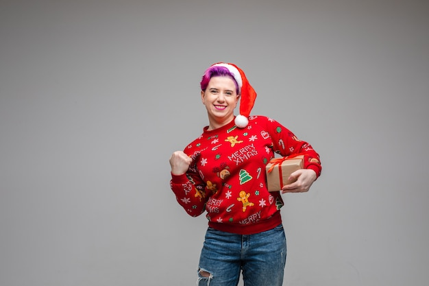 Happy caucasian woman in santa hat and winter jersey and jeans clenching her fist and holding wrapped christmas gift and smiling