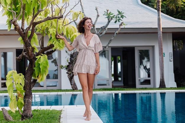 Felice donna caucasica in abito estivo corto fuori villa hotel da una struttura ad albero e piscina blu