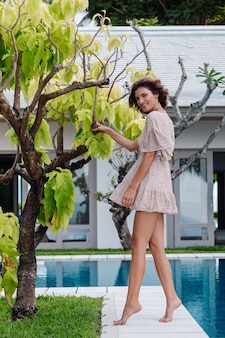 Happy caucasian woman in short summer dress outside villa hotel by tree and blue swimming pool