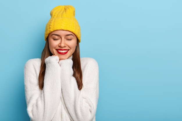 행복한 백인 여자는 유쾌하게 미소를 짓고, 붉은 색으로 칠한 입술을 가지고 있으며, 손을 턱 아래에 유지하고, 아늑한 하얀 겨울 스웨터와 노란 모자를 쓰고, 눈을 감고, 파란색 배경 위에 절연하고, 운이 좋다고 느낍니다.