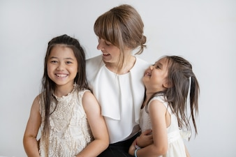 Happy Caucasian woman spending time with pretty little daughters