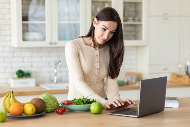 幸せな白人女性は、ラップトップと健康食品のセットを持って家庭の台所に立って、ダイエット食品を調理するためのレシピをインターネットで探します