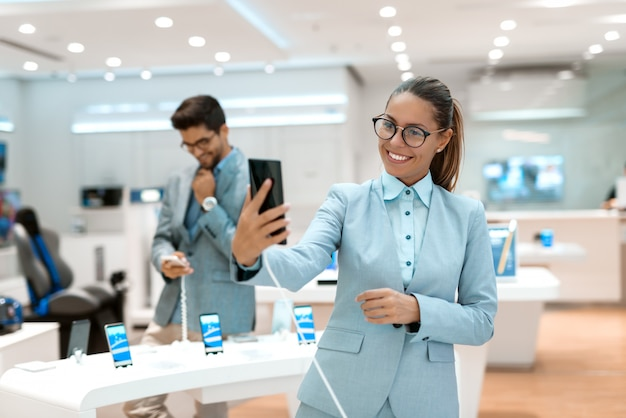 Happy caucasian woman taking self portrait with new smart phone while standing in tech store. in background her husband trying out smart phone. tech store interior.