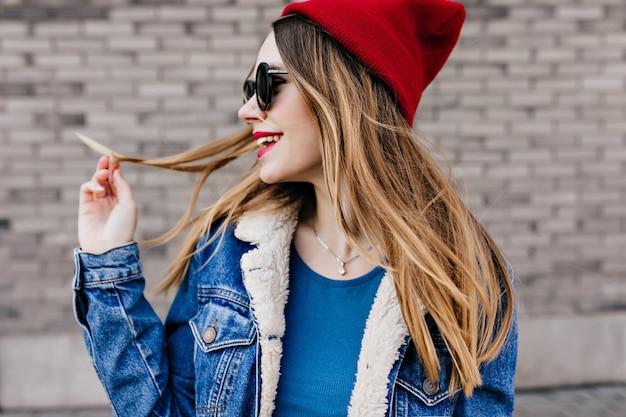 寒い春の日に屋外で時間を過ごす薄茶色の髪の幸せな白人女性。街歩きを楽しんでいる赤い帽子と黒い眼鏡のかわいい女性モデルの肖像画。