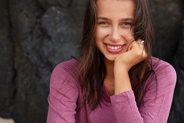 Felice donna caucasica con espressione compiaciuta, guarda con gioia, ha gli occhi verdi, capelli lisci scuri