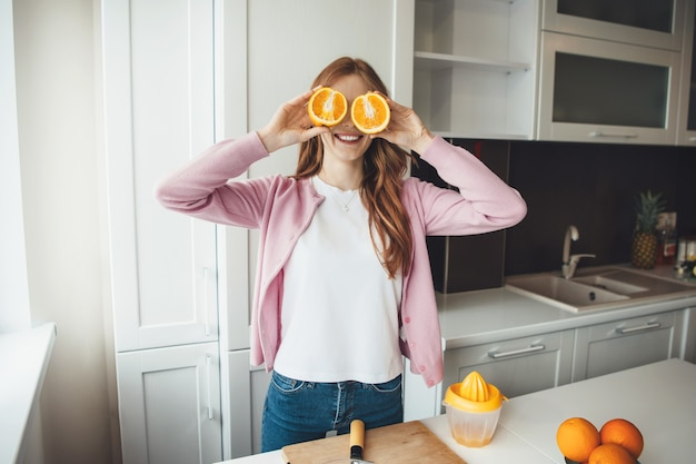 Happy caucasian woman with red hair covering her eyes with sliced oranges while making fruit juice