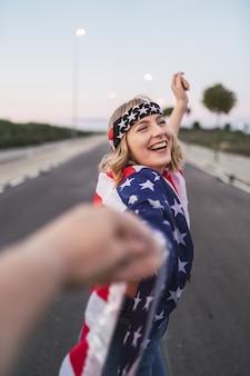 Счастливая кавказская женщина с короткими светлыми волосами и флагом сша держит руку во время прогулки по дороге
