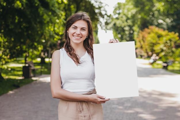 Счастливая кавказская молодая брюнетка женщина держит в руках плакат и улыбается на фоне парка
