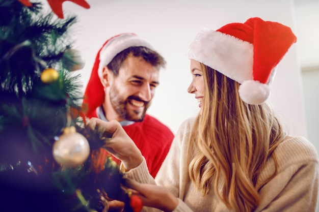 Happy caucasian young couple with santa hats on heads decorating christmas tree while standing in living room.