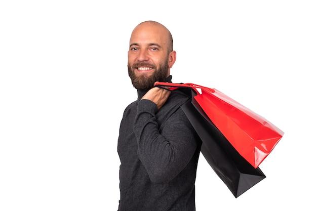 幸せな白人の若い男は、白い背景の上の彼の肩に買い物袋を運ぶブラックフライデー