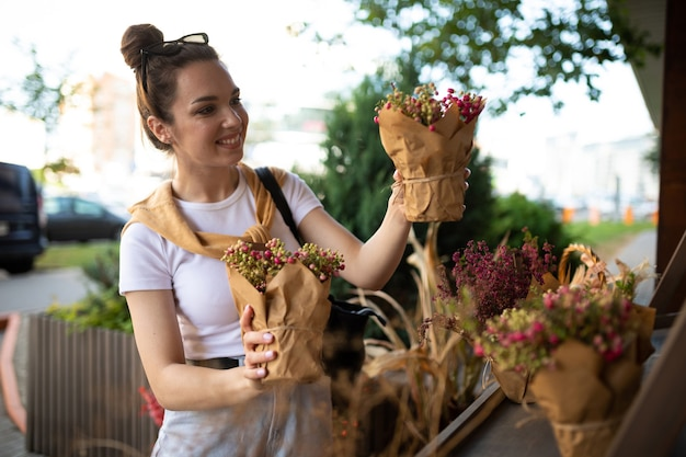 幸せな白人の若い女性は、屋外の庭の屋台で購入する鉢植えの花を選びます。